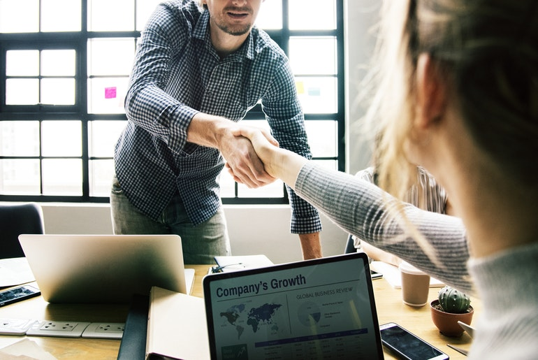 Man Shaking Hand With Woman Over Business Deal