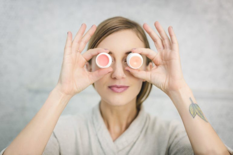 Woman holding up pots of cream to her eyes