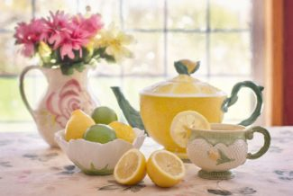 Teapot with bowl of lemons, limes and a cup of lemon tea
