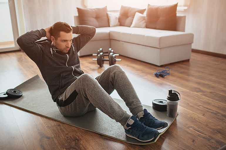 Man exercising at home on the living room floor